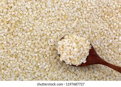 Spoon of rolled white Quinoa seed gluten-free flakes. Flattened organic grains high in protein, dietary fiber, B vitamins, dietary minerals (Chenopodium Quinoa)