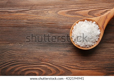 Spoon with sea salt on wooden background