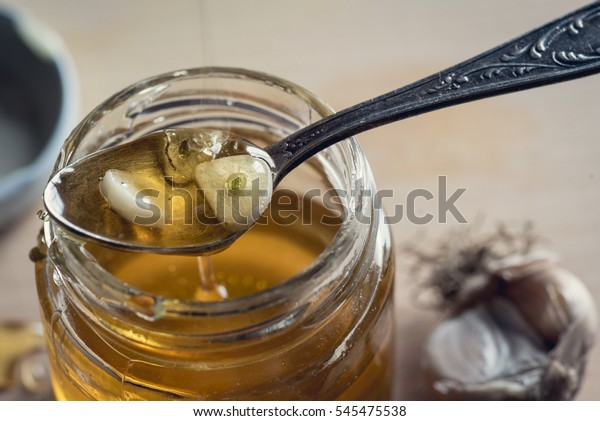 Spoon with sliced garlic cloves in honey over the opened honey jar