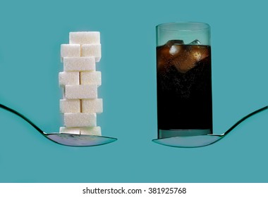 spoon with stack of sugar cubes piled  compared with cola refresh drink in sweet excess calories content,  diet and glucose addiction concept isolated on blue background