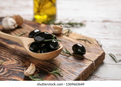 Spoon with tasty olives on wooden board