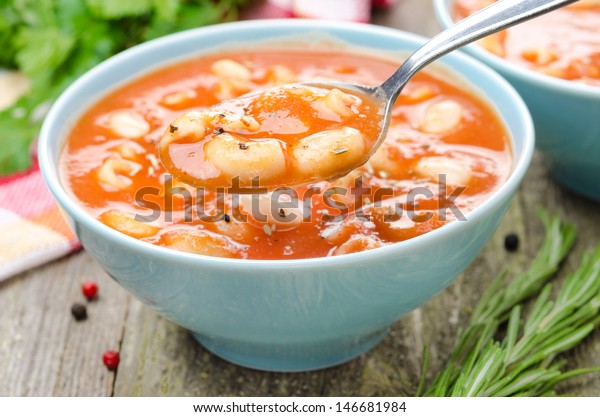 spoon of tomato soup with pasta, white beans and rosemary, close-up