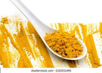 A spoon of Turmeric powder on white background, closed up, top view