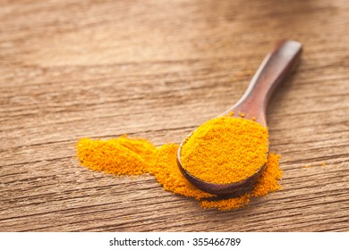 A spoon of turmeric powder on wooden texture, asian spice and herb