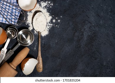 spoon with wheat flour and baking ingredients on a black background, top view closeup