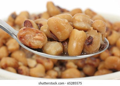 Spoonful of black eyed peas in the foreground with a large serving of black eyed peas in a bowl in the background.