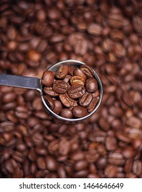 Spoonful of coffee beans lifted high out of bag, with background blurred