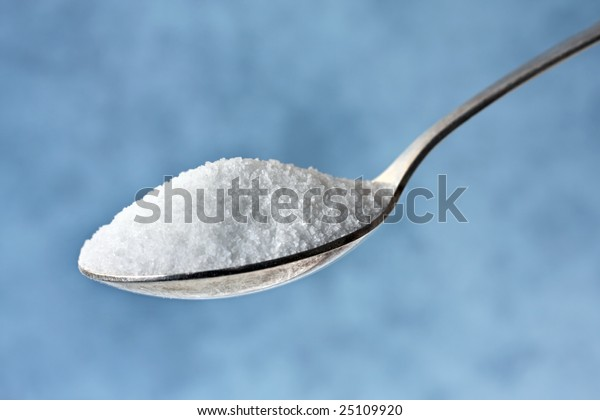 Spoonful of sugar, with blurred pastel blue background.