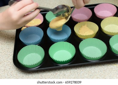 spooning cake mixture into colourful cake cases in baking tray.
