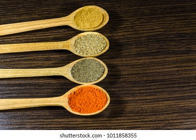 Spoons with different spices on dark wooden table. Top view