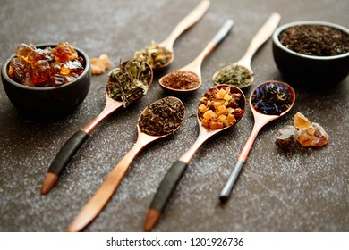 Spoons with different types of dry tea leaves on rusty dark background. Top view.