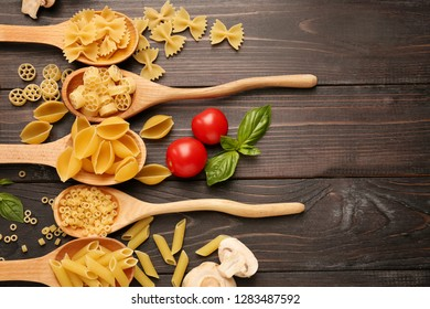 Spoons with different types of raw pasta on wooden background