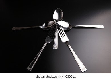 spoons and forks  against a black background as a man