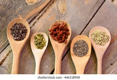 Spoons full of super foods on a rustic wooden table