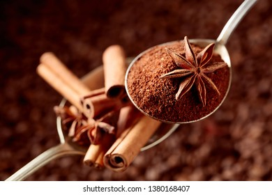 Spoons of ground coffee and anise with cinnamon sticks on the background of coffee beans. Selective focus.