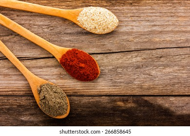 spoons with spices on a wooden board