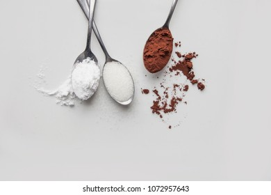 Spoons with sugar, cocoa and flour on white background. Cooking Flat Lay. Pastry Chef table. Ingredients Top view. Space for text. Clouse up.