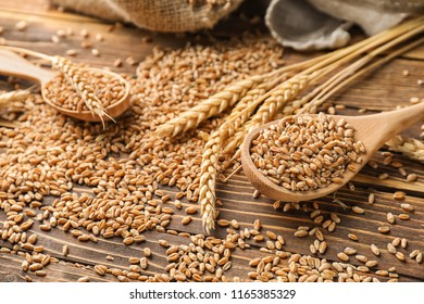Spoons with wheat grains on wooden background, closeup