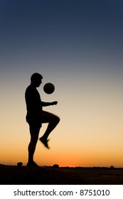 sporman's siluetthe is playing football and practising with the ball