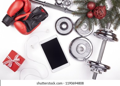 Sport accessories.  Dumbbells, gloves, sneakers,  computer tablet, fir tree branches and Christmas decorations  on a white background.  Top view with copy space. Fitness, sport and healthy lifestyle.