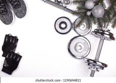 Sport accessories.  Dumbbells, gloves, sneakers, fir tree branches and Christmas decorations  on a white background.  Top view with copy space. Fitness, sport and healthy lifestyle concept.