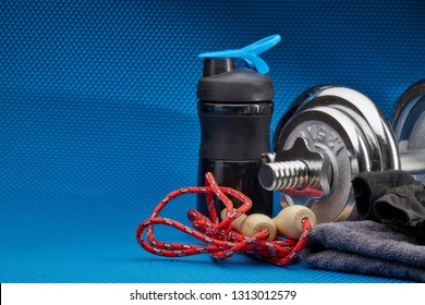 Sport accessories. Steel dumbbells, gloves and skipping rope on a blue background. Fitness, sport and healthy lifestyle concept.
