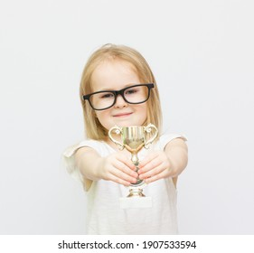 Sport achievement. Celebrate victory. Girl hold golden goblet. Importance of capturing evidence of kids progress. Proud of her achievement. Celebrating childrens achievements great and small.