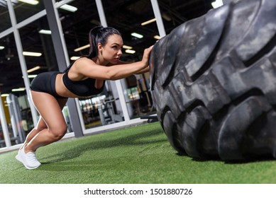 Sport active girl make workout on a gym with heavy equipment - tyre training. Sexy fitness woman, with black hair.