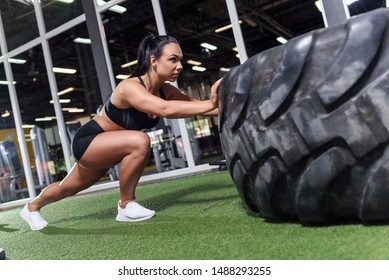 Sport active woman focus on workout on a gym with heavy equipment - tyre training. Sexy fitness girl, with black hair.