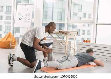 Sport activities. Nice professional doctor looking at his patient while helping him to do a physical exercise
