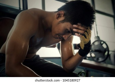 Sport asian man feeling depressed,tired about unsuccessful excercise,workout in gym.Adult bodybuilder sitting and taking a break after difficulty training.Exercise and Sport man concept.