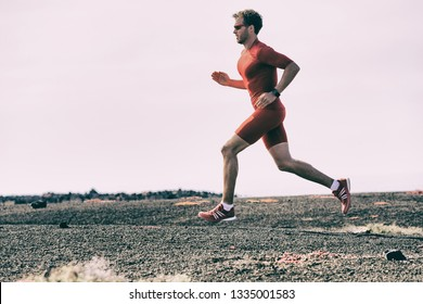 Sport athlete training run on outdoor workout doing cardio workout on running trail outside - Triathlon runner man on run race marathon in summer. Fitness and sports active male jogging.