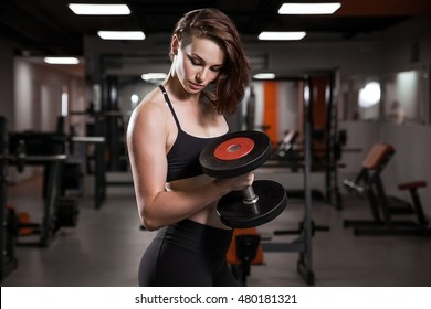 Sport. Athletic fitness woman pumping up biceps with dumbbells. Redhead sexy fitness girl in black sport wear training set. Fitness woman in the gym.