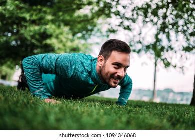 Sport. Athletic man doing push-ups outdoors.