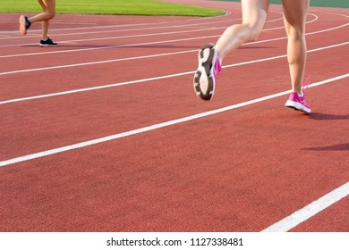 Sport. Athletic people running on the track field. Closeup of legs of a track runners. Concept run