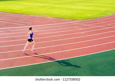 Sport. Athletic young woman in pink sneakers run on running track stadium. Concept run