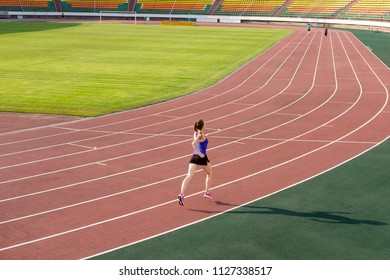 Sport. Athletic young woman in pink sneakers run on running track stadium. Concept run. Run competition on stadium.