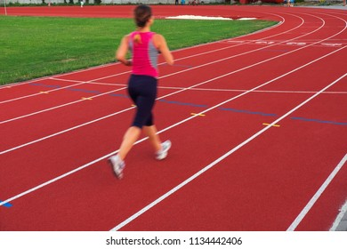 Sport. Athletic young woman in sneakers run on running track stadium. Concept run.