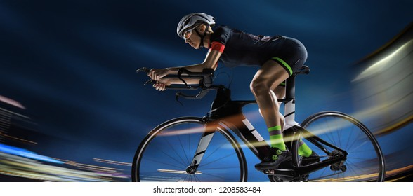 Sport background. Athletic woman cycling road bike in the evening. Dramatic view of the night city.