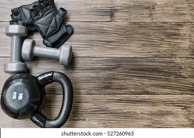 Sport background with copyspace. Top view  of grey dumbbells ,black kettlebell and workout gloves. Weight lifting exercise concept.
