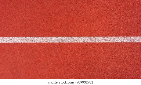 Sport Background. Decorative coating at the stadium in outdoor. White line in red sporting a rubberized Jogging track on the street stadium, view from above