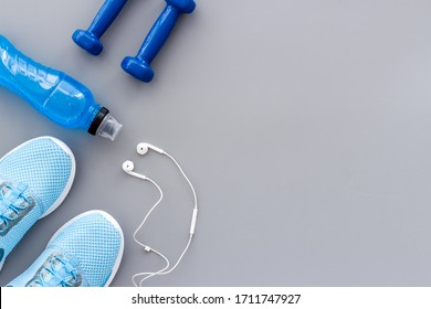 Sport background with sneakers and dumbbells on grey table top view copy space