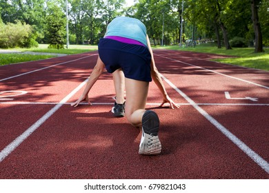 Sport backgrounds. Female sprinter starting on the running track.