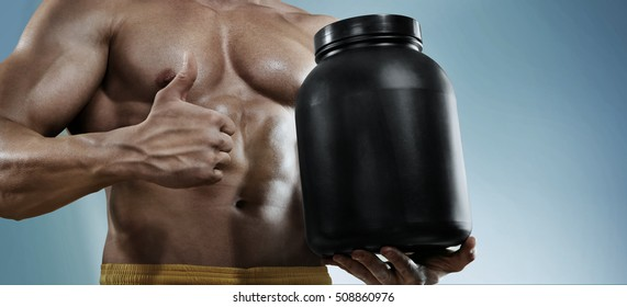 Sport backgrounds. Strong bodybuilder holding a plastic jar with a dry protein and showing gesture.  Isolated. Sport food