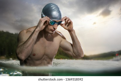 Sport backgrounds. Young athletic swimmer standing near the sunset river.