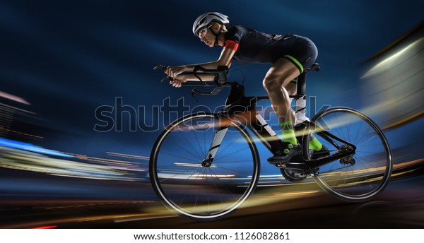 Sport backgrouns. Athletic woman cycling road bike in the evening. Dramatic view of the night city.