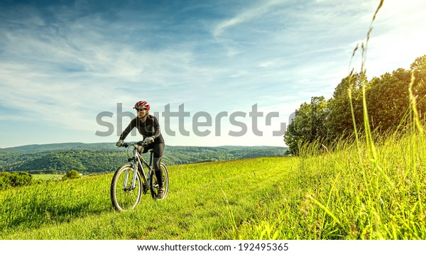 Sport bike woman in a beautiful meadow, fabulous scenery
