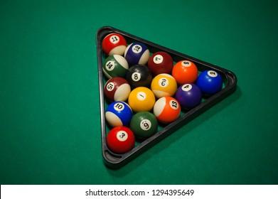 Sport billiard balls set arranged in shape of triangle on green billiard table in pub