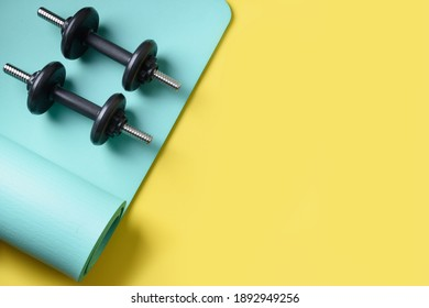 Sport black dumbbells on turquoise yoga mat on yellow background. Copy space. Flat lay. View from above.