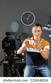 Sport blogger with cup of coffee recording video on camera at home